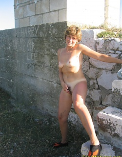 Amateur mature with hairy pussy is posing nude near the building