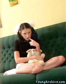 Teenie girl with pigtails in schoolgirl uniform is showing her shaved pussy