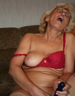 Lusty blonde grandmom is masturbating with dildo on a chair